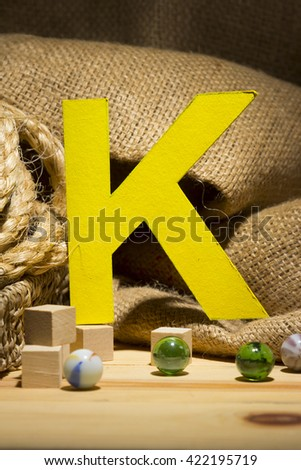 "The letter "" K "" by  Photo font "" Yellow Texture "" and subjects with active texture. Wood, burlap, glass beads. Preparation for graphic design"