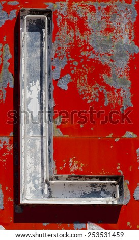 """The letter """"L"""" on a vintage antique, broken neon sign with red background - stock photo"""