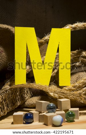 "The letter "" M "" by  Photo font "" Yellow Texture "" and subjects with active texture. Wood, burlap, glass beads. Preparation for graphic design"