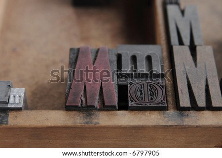 the letter M in different sizes and fonts in a wood type case, focus on the intricate, decorative metal M - stock photo