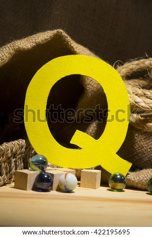 "The letter "" Q "" by  Photo font "" Yellow Texture "" and subjects with active texture. Wood, burlap, glass beads. Preparation for graphic design"