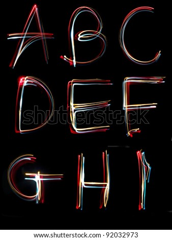 the letters, a,b,c,d,e,f,g,h and i written in the dark with torches and lasers - stock photo