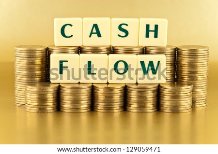 The letters  CASH FLOW with stacks of coins on gold background