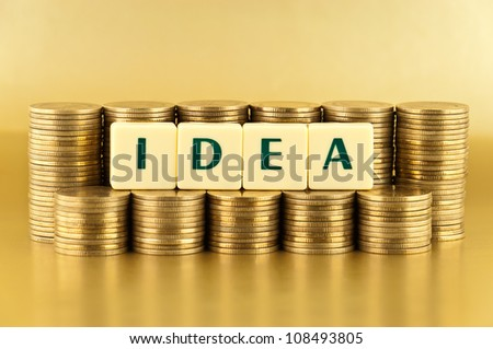 the letters IDEA with stacks of coins on gold background