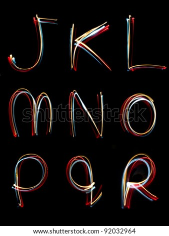 the letters, j,k,l,m,n,o,p,q, r written in the dark with torches and lasers - stock photo