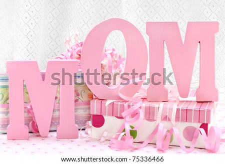 The letters MOM standing in front of pretty and feminine wrapped gifts.  The white lace curtain in the background has room for copy space. - stock photo