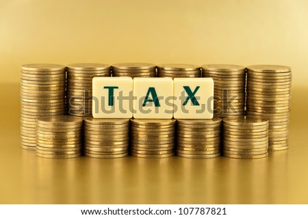 the letters TAX with stacks of coins on gold background - stock photo