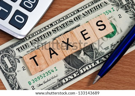 The letters TAXES on  dollar banknote business concept - stock photo