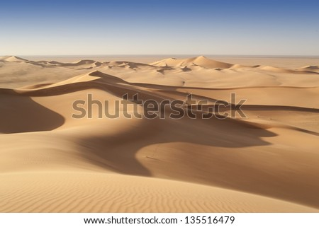 The Libyan desert - a fantastic place for travelers and photographers. Rocks of an unusual form, beautiful structure of dense yellow sand, dune of the huge sizes and deep sky of Sahara. - stock photo