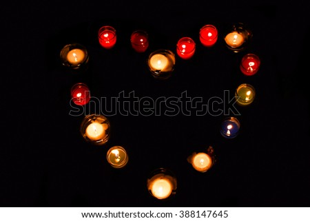 the light heart shaped from the candles on black background - stock photo