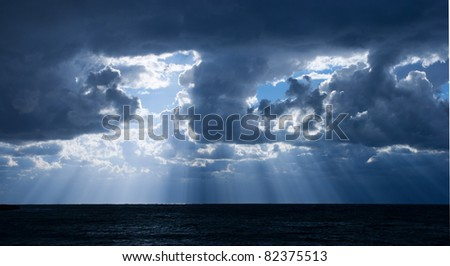 The light rays through the clouds over the sea - stock photo