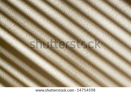 The light shining in through the blinds, creating an interesting pattern on the textured wall.