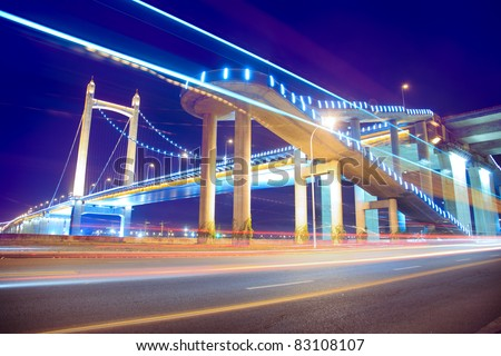 the light trails on the modern suspension bridge background at twilight  in china. - stock photo