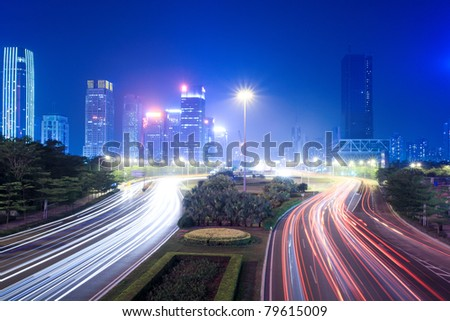 the light trails on the street with modern city background at night - stock photo