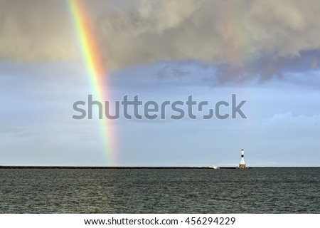 The lighthouse at Conneaut, Ohio is graced by a rainbow over Lake Erie. - stock photo