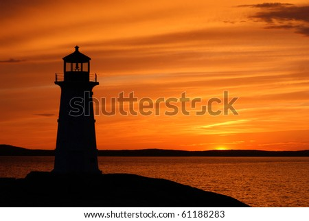 The lighthouse at Peggy's Cove, Nova Scotia at sunset. - stock photo