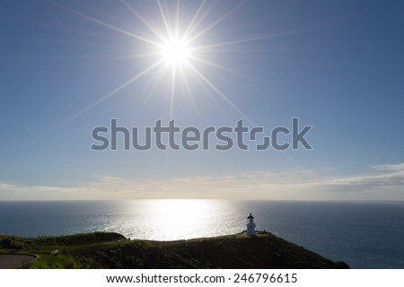 The lighthouse of Cape Reinga in the Far North, New Zealand. Shot in backlight with the sunstar. Natural landmark, where Tasman Sea meets Pacific Ocean. - stock photo