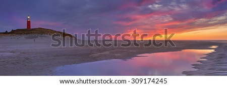 The lighthouse of the island of Texel in The Netherlands at sunset. Photographed from the beach below, with the sunset colours reflected in a tidal pool. - stock photo