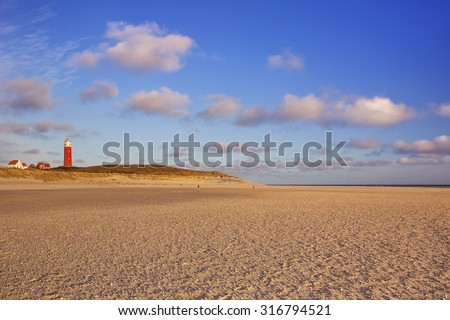 The lighthouse of the island of Texel in The Netherlands in beautiful early morning sunlight. Photographed from the wide beach below. - stock photo