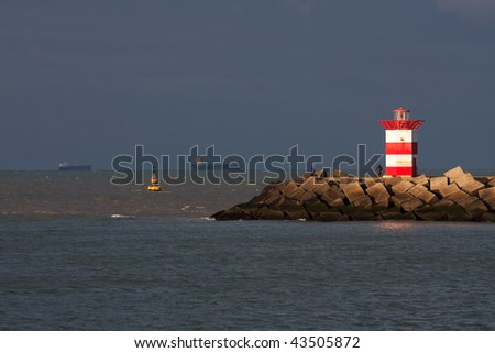 The lighthouse on the pier in IJmuiden (Netherlands) lights up in the afternoon sun. - stock photo