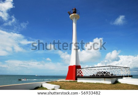 The lighthouse with boats passing by in Belize City (Belize).