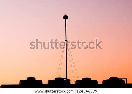 The lightning rod on the roof-tile taken when sunset - stock photo