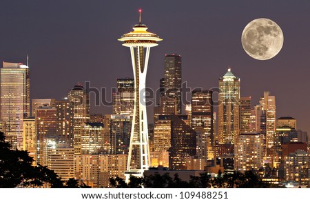 The lights come on in Seattle with a full moon - stock photo