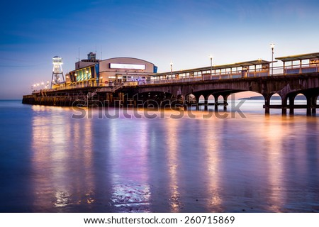 The lights of Bournemouth Pier at night reflected in the wet sand on the beach. Dorset  England UK Europe. - stock photo