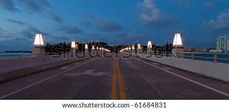 The Lights of Star Island Bridge nearing Miami Beach off MacArthur Causeway shortly after sunset. - stock photo