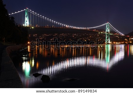 The lights of the Lions Gate Bridge reflect in Burrard Inlet. Seen from the seawall surrounding Stanley Park. Vancouver, British Columbia. - stock photo