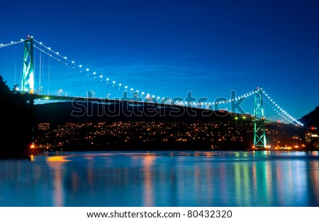 The Lion's Gate Bridge in Vancouver, British Columbia during an evening blue hour. - stock photo