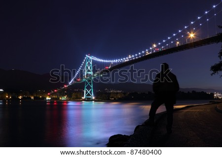 The Lions Gate bridge at twilight. A pedestrian takes in the view from the seawall which surrounds Stanley Park. Vancouver, British Columbia, Canada. - stock photo