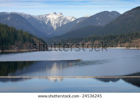 The Lions (peaks) reflected in Capilano Lake, North Vancouver on a winter day. - stock photo