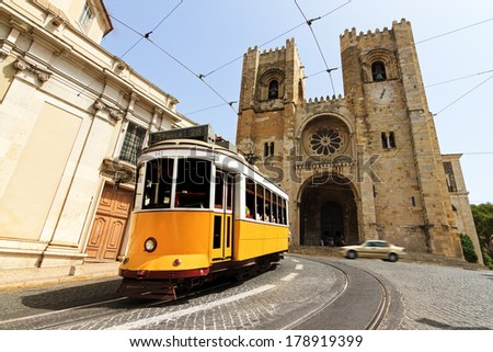 The Lisbon Cathedral with a traditional yellow tram in Lisbon, Portugal - stock photo