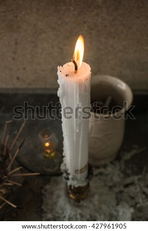 The lit candles in church against a dark background