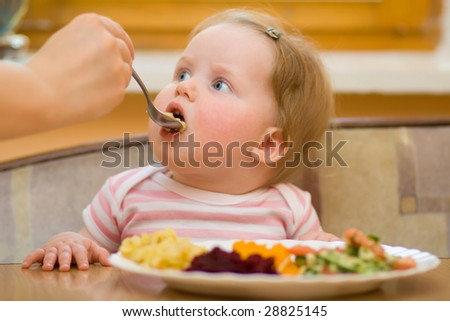 The litle child eats a vegetable salad - stock photo