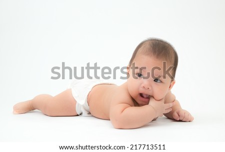 the little asian boy wears white diaper, lies on stomach and sucks the finger