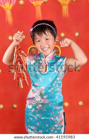 The little asian girl is in Chinese style clothes holding firecracker.
