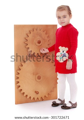 The little blonde girl in a short red knitted dress came with their parents for the first time in a Montessori kindergarten. Girl develops a toothed wheel which is in the class as a sample.-Isolated - stock photo