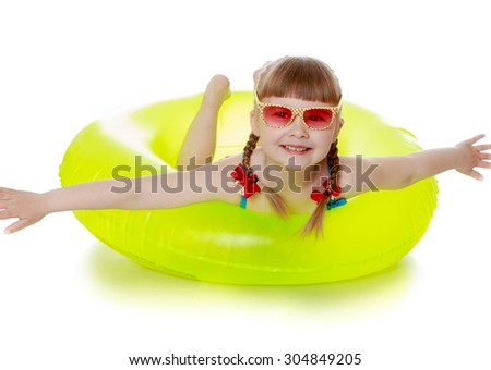 The little blonde girl in the pink glasses. The girl is in a swimsuit on a yellow rubber ring for swimming, spreading their arms . The girl is vacationing with his parents in the seaside resort - stock photo
