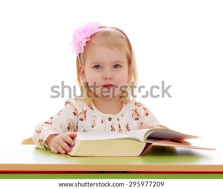 The little blonde girl with bow on her head is reading a thick book while sitting at a Desk, close-up - isolated on white background - stock photo