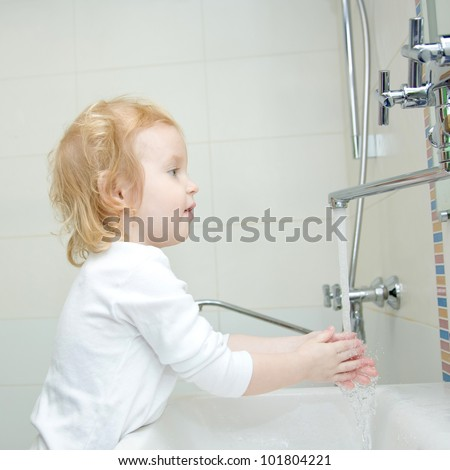 The little blonde happy smiling girl washing hands and face with soap in the bathroom. Hygiene. The girl wearing a blank white shirt. Ready for your design or logo