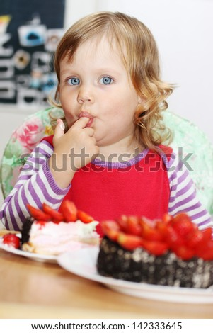 The little blue-eyed girl eating cake with strawberries
