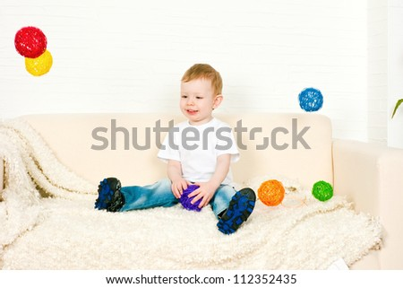 The little boy and flying multi-colored spheres