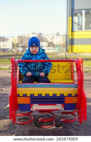 The little boy at a playground plays on the children's machine - stock photo