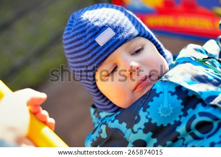 The little boy at a playground shakes on a swing - stock photo
