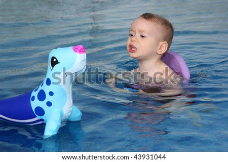 The little boy bathes in pool - stock photo