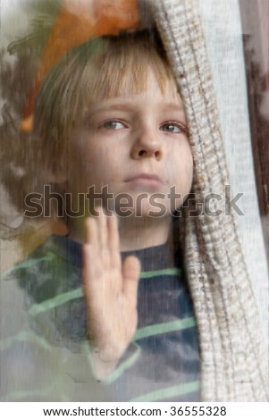 The little boy behind a wet window - stock photo