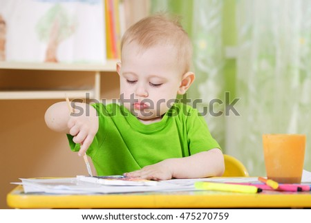 The little boy draws paints