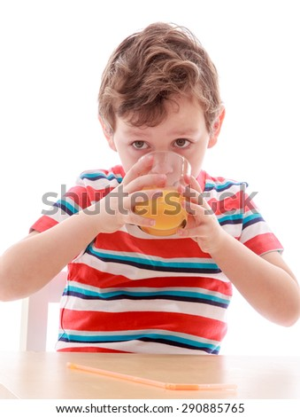 The little boy eagerly drinking juice from a glass , close-up - isolated on white background - stock photo